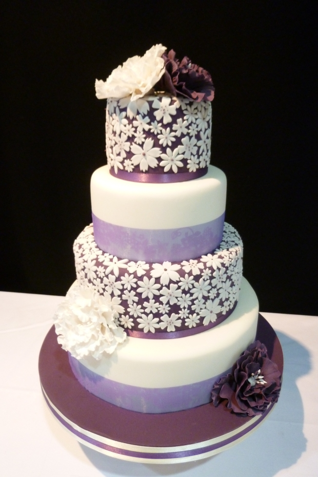 Wedding cake with purple background and white petals - photo by Naomi Longworth